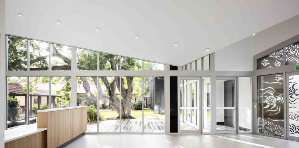 Interior of a beautiful medical centre with a glass wall looking out to a garden