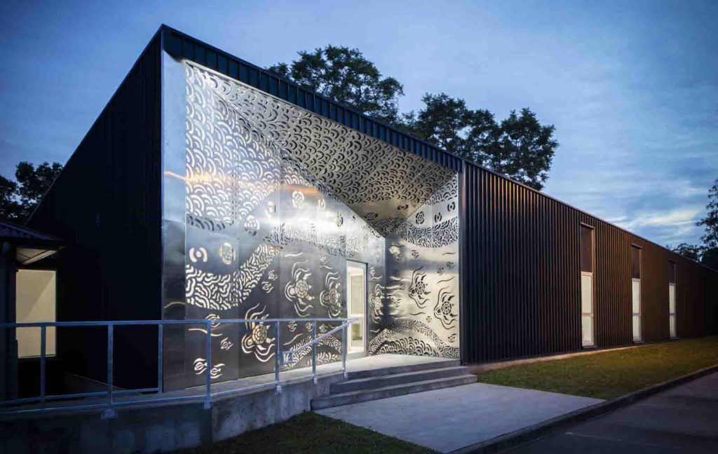 Evening light, a building whose entry is through an Aboriginal art screen facade