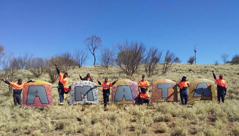 Eight Anangu people pose next to a huge sign for the community of Amata, which is made from car bonnets