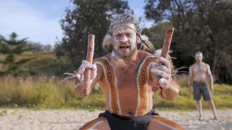 Gumbaynggirr man dressed for ceremony, holding clapsticks, facing camera