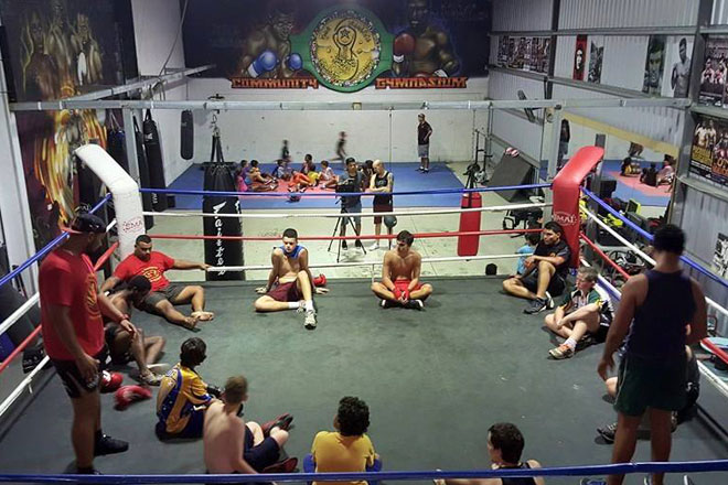 A boxing ring with a group of young Aboriginal men seated in a circle and two older men standing