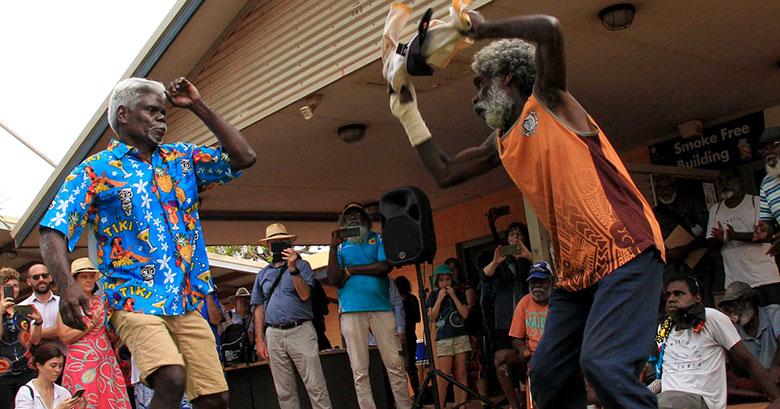 Two men dancing to celebrate community-controlled health at Mala'la Health Service Aboriginal Corporation in Maningrida