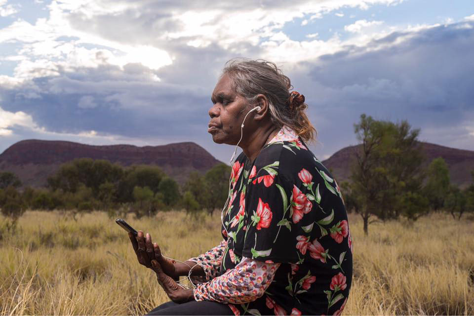 Woman sitting with her eyes closed listening to a guided meditation in central Australia
