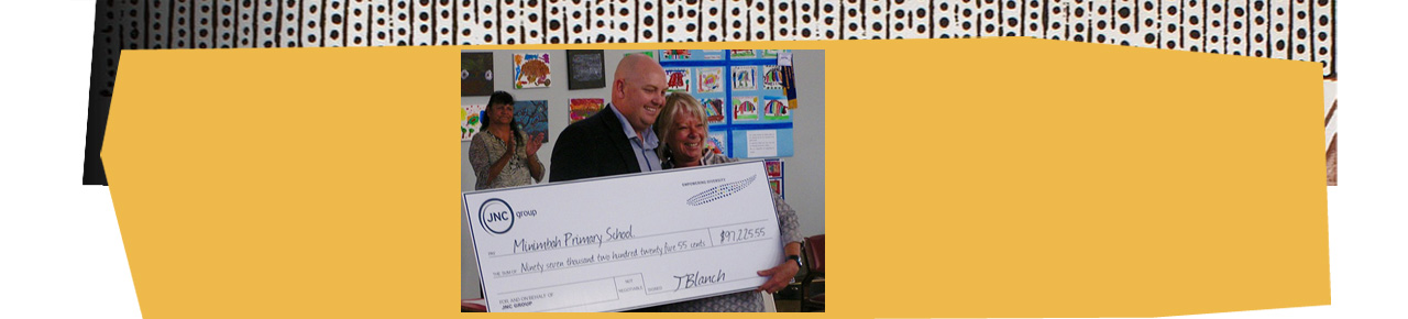 local contractor JNC group's Jeremy Blanch presenting over  $97,000 to the school's executive principal, Jenny Brown,