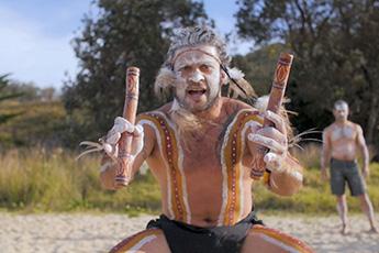 Gumbaynggirr man dressed for ceremony, holding clapsticks, facing camera