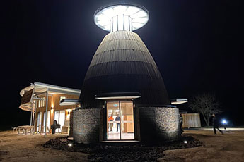 Night view of a round stone and timber building