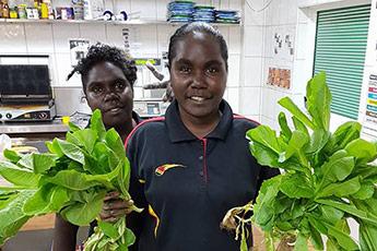 Young Yolngu women in a shop holding salad greens