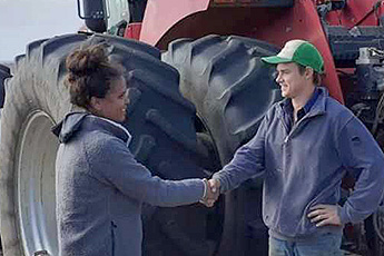 Handshake in front of a tractor
