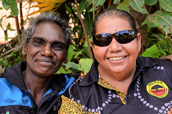 Two women smiling to camera in front of greenery, Maningrida