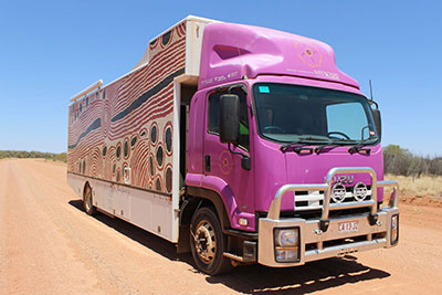 Truck with its cabin painted purple and its side painted with Aboriginal art