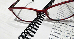 Red-rimmed glasses sitting on a binder showing a schedule of times