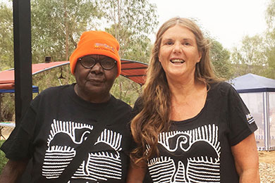 Aboriginal woman in an orange beanie standing with a white woman. Both wear matching black Tshirts with a white design of a bird