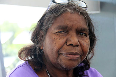 Close-up face of Irene Nangala, a shrewd-looking Aboriginal woman with reading glasses on her head