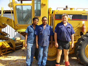 Left (Stanley Till Junior - Walmajarii) Middle (Matt Murray - Walmajarri) Right (Ian Pateman) standing outside the Marra Worra Worra Workshop, Fitzroy Crossing
