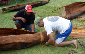 Cameron Andy and Jonathan Hill secure an end of one of the canoes with bark strips. Photo: David Payne/ANMM