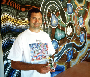 Craig McVee, a director of Kojonup Aboriginal Corporation, putting the finishing touches on the mural, entitled Creation—Six Seasons, which hangs in the foyer.