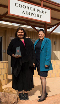 Photo: At Coober Pedy airport: UTHSAC's Glenys Dodd (left) after receiving the Gladys Elphick Award in Adelaide for her dedication and commitment to Aboriginal health with Priscilla Larkins, UTHSAC's CEO, who, on a separate occasion, won the Aboriginal nurses/midwife category of the 2013 South Australian Nursing and Midwifery Excellence Awards. Photo courtesy UTHSAC