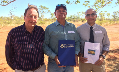 University of Queensland professors Paul Memmott (left) and Mark Western (right) exchange signed copies of the spinifex research agreement with Dugalunji Aboriginal Corporation managing director, Colin Saltmere (centre)