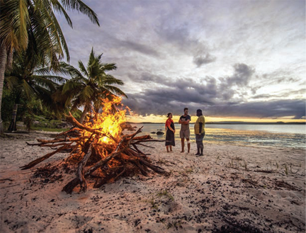 Bon fire on beach with three people standing around it