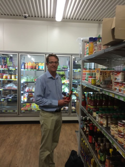 Anthony beven holding a bottle of tomato sauce inside the store
