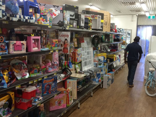 Shelves full of toys in the Kaljitti store with a boy walk past the toys
