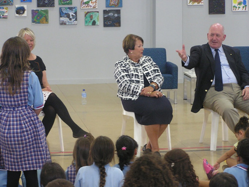 The Governor General Sir Peter Cosgrove and Lady Cosgrove  sitting infront of a group of children, answering questions.