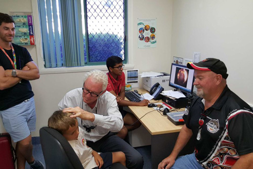 Boy sitting in a chair getting his ear checked by a doctor
