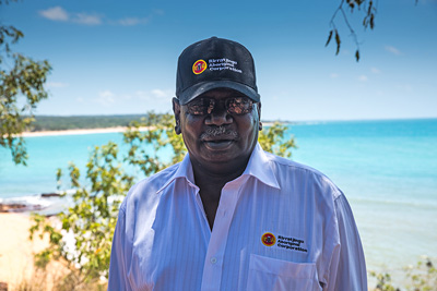 Bakamumu Marika, chair of the board of Rirratjingu Aboriginal Corporation, with a beach in the background