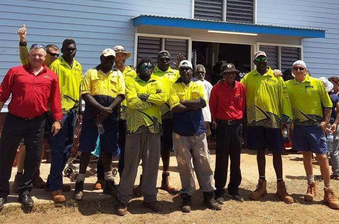 12 construction workers, mostly Yolngu men, standing in front of a building