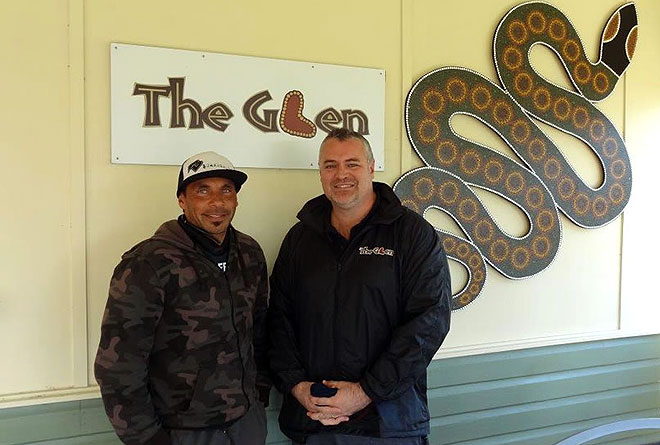 Two men standing in front of a sign for 'The Glen' and a large decorative snake