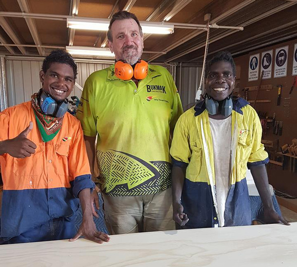 Two young Yolngu men, cabinet-maker apprentices, smiling, with an older white man