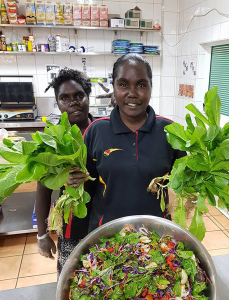 Two young Yolngu women in a shop, one holding salad greens, in front of a large bowl of salad