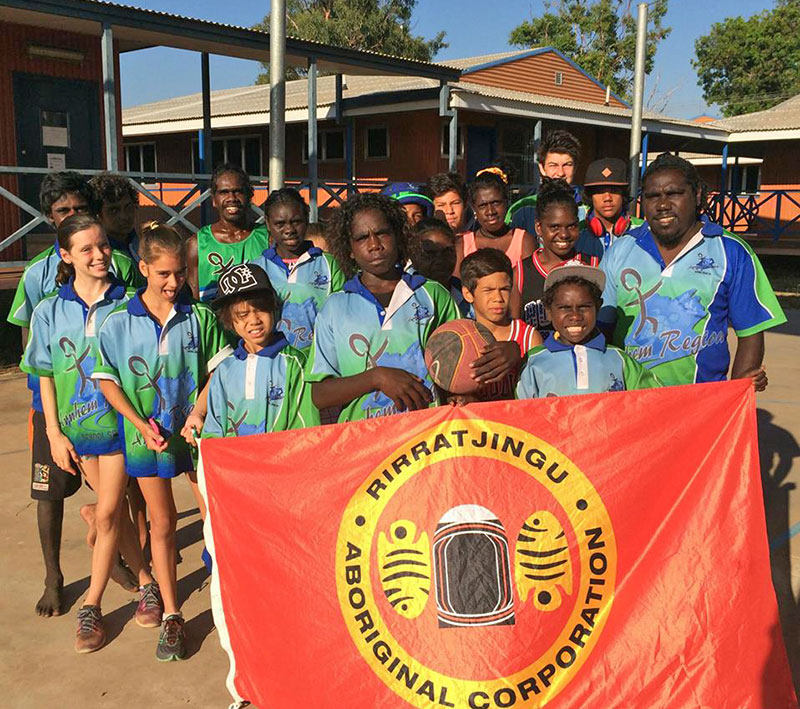 Group of young Yolngu athletes standing with a man in front of a flag of Rirratjingu Aboriginal Corporation