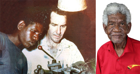 Young Aboriginal man looking at machinery with a white man, and as an older man, in a red shirt, looking at the camera