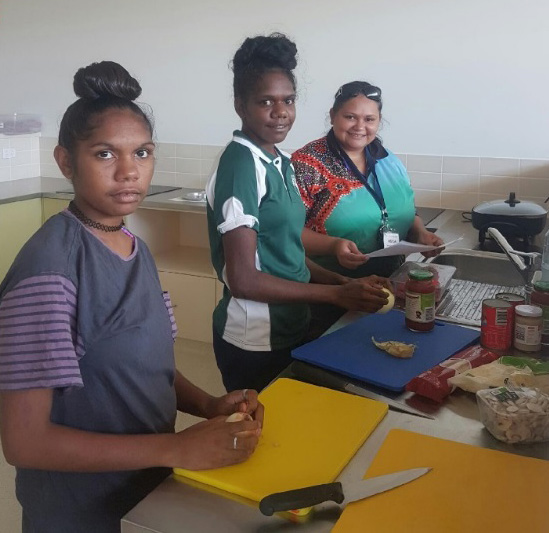Two young Aboriginal women prepare fresh food in a kitchen while a third woman looks on