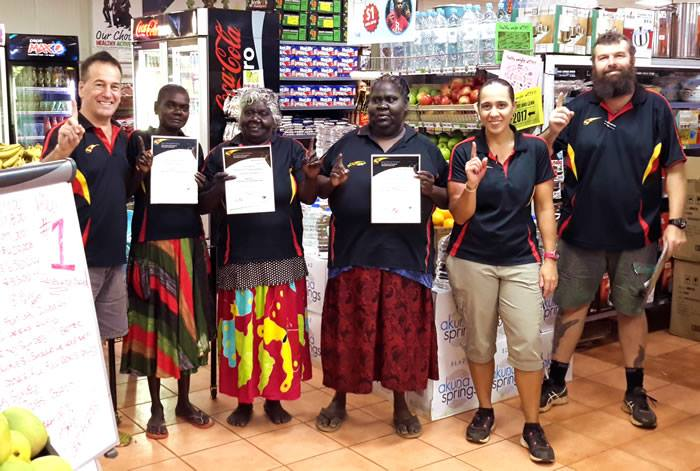 Six people in a shop, three holding certificates