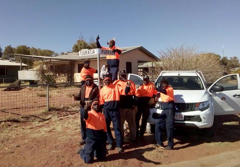 Eight men celebrating the first street signs for a community in the APY Lands