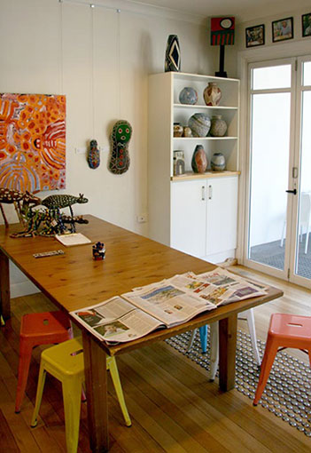 Brightly lit cafe with Aboriginal art works on the walls and shelves