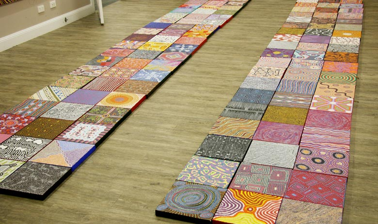 Six rows of small Aboriginal paintings displayed on a gallery floor
