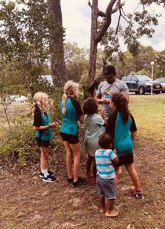 Group standing under a tree; man showing children wombat berries