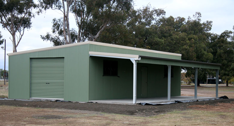 Green colourbond shed under tall trees