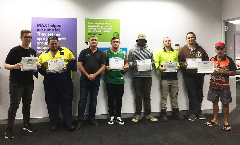 Seven Aboriginal construction workers receive their Certificate II; an eighth man stands with them