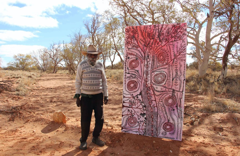 Peter Mungkuri standing next to a large pink and black painting at Iwantja, 2020