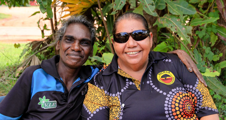 Two women smiling to camera, one with her arm around the other. Greenery behind them