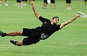 Man in black diving for a frisbee on a grass playing field