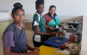 Young Aboriginal women preparing food in a kitchen