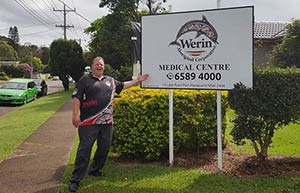 man standing proudly in front of a sign for Werin Aboriginal Corporation