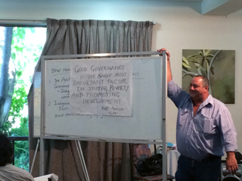 Russell Styche standing next to a white board with writing about good governance on it.