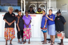 Laundry staff and corporation directors in front of the self-contained laundry