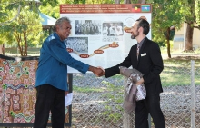 Two men shaking hands in front of signage about a garden of reflection and healing